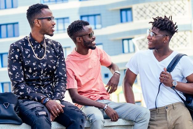 路上で通信する3人のファッショナブルなクールなアフリカ系アメリカ人の男の学生のグループ