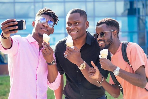 Группа из трех друзей-афроамериканцев ест мороженое в вафельном рожке и фотографирует селфи по телефону летом в парке