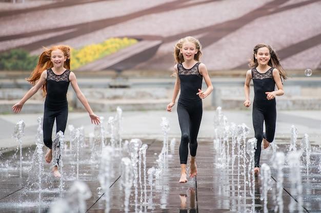 검은색 꽉 끼는 옷을 입은 세 명의 작은 발레리나 그룹이 더운 날 도시 경관을 배경으로 분수가 튀는 가운데 관객에게 달려갑니다.