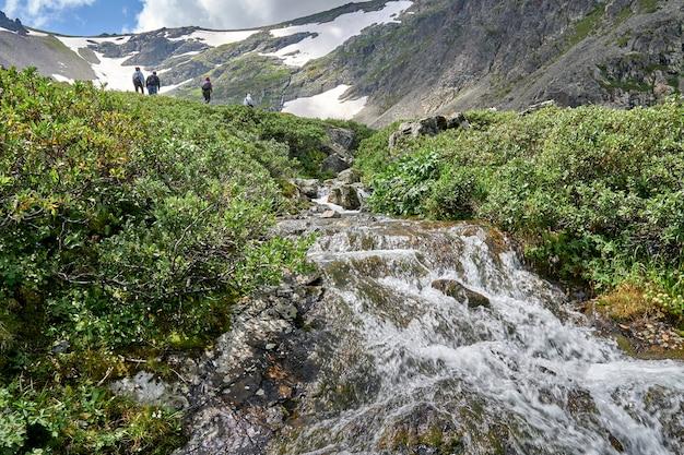 Группа туристов поднимается на вершину горы, проходя мимо горной реки.