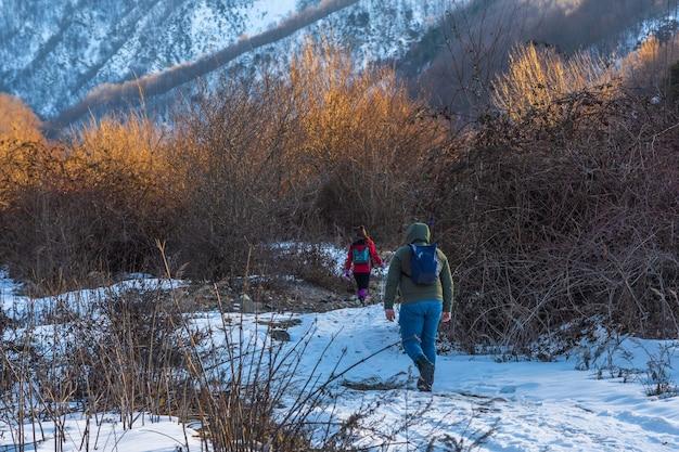 観光客のグループが山でハイキングに行きます