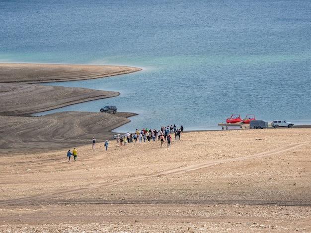 観光客のグループがボートに乗り込みに行きます。リモートビュー。ダゲスタン共和国のスラク貯水池。