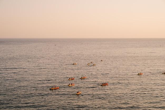 관광객 그룹은 일몰 하늘을 배경으로 바다로 쌍을 이루는 카약 여행