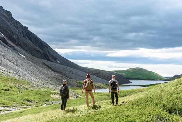배낭을 메고 있는 한 무리의 관광객들이 함께 서서 산을 바라보고 있다
