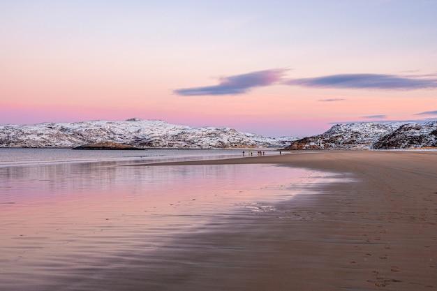 ビーチで遠くにいる旅行者のグループ。北極海の美しいピンクの夕日。