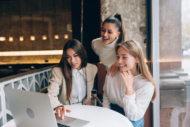 Группа подруг в кафе смотрит на ноутбук