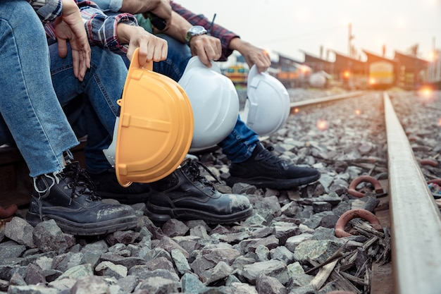 Группа рабочих в каске и инженеров отдыхали на рельсах после тяжелой работы.