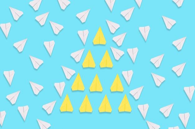 노란 종이 비행기 무리가 의도적으로 흰 비행기 사이를 날아갑니다. 파란색 배경입니다. 플랫 레이. 리더십과 팀워크의 개념입니다.