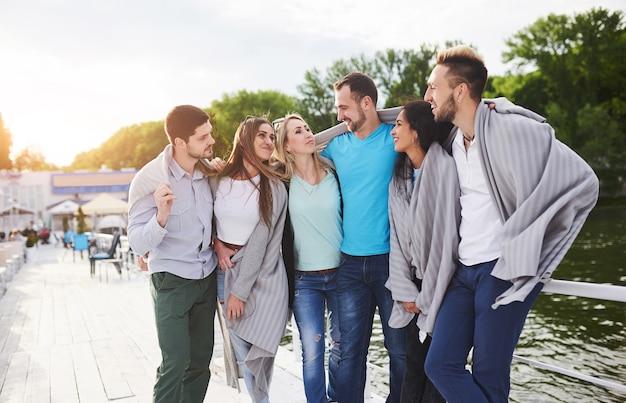 太陽の下で桟橋で休暇中に若くて成功した人々のグループ。