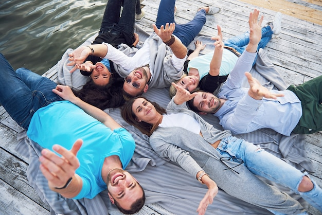 Группа молодых и успешных людей на отдыхе друзья играют на озере. позитивные эмоции.
