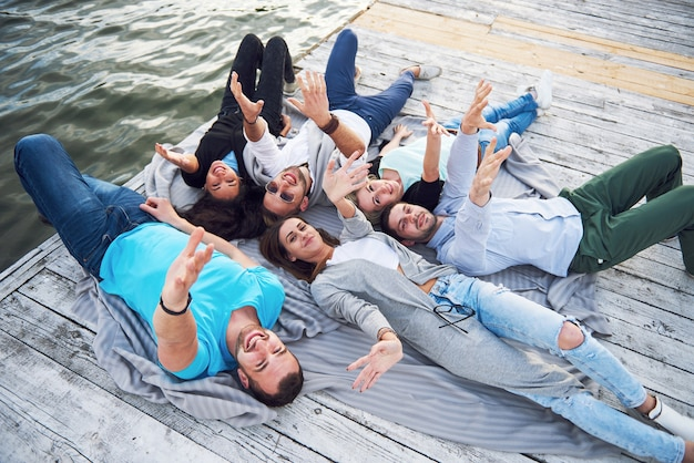 湖でゲームを楽しんでいる休暇中の若くて成功した人々のグループ。ポジティブな感情。