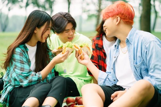 Группа молодых азиатов с удовольствием ест бутерброды в парке