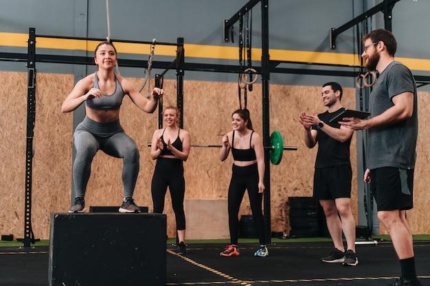 トレーナーやグループの他のメンバーが応援している間、さまざまな運動ルーチンを行うクロスフィットジムの若いアスリートのグループ