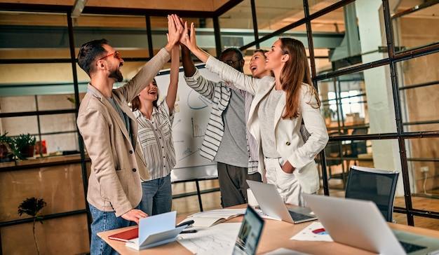 Группа молодых деловых людей обсуждает бизнес-план на доске в современном офисе.