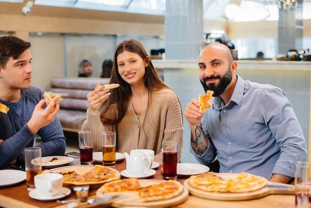 쾌활한 젊은 친구들이 카페에 앉아 피자를 먹으며 이야기하고 있습니다. 피자 가게에서 점심.