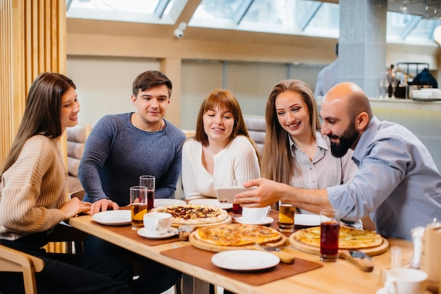 Группа молодых веселых друзей сидит в кафе, разговаривает и ест пиццу