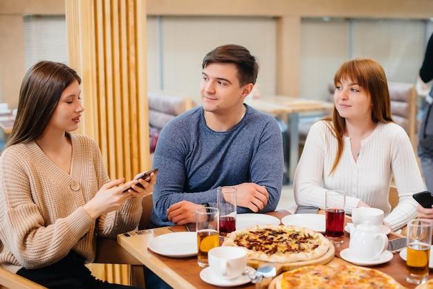 쾌활한 젊은 친구 그룹이 카페에 앉아 이야기하고 전화로 셀카를 찍고 있습니다. 피자 가게에서 점심.