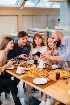 쾌활한 젊은 친구 그룹이 카페에 앉아 전화로 이야기하고 셀카를 찍고 있습니다.