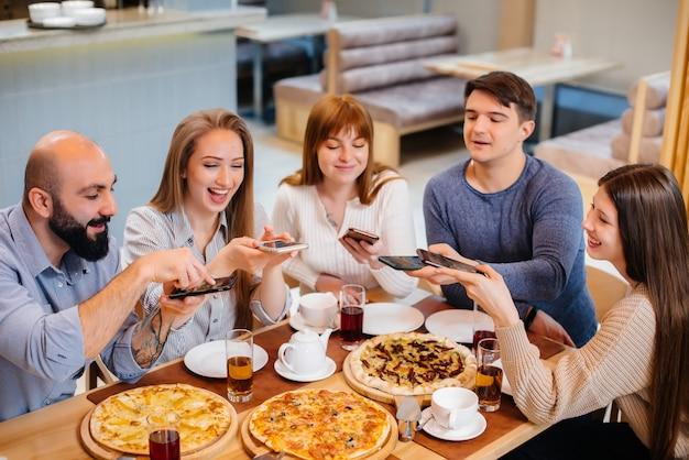 쾌활한 젊은 친구들이 카페에 앉아 전화로 셀카를 찍고 있다