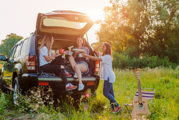 쾌활한 젊은 여성 그룹이 자동차로 자연을 여행합니다.