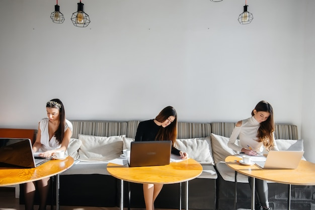 Группа девушек сидит в офисе за компьютерами и обсуждает проекты. общение и обучение онлайн.
