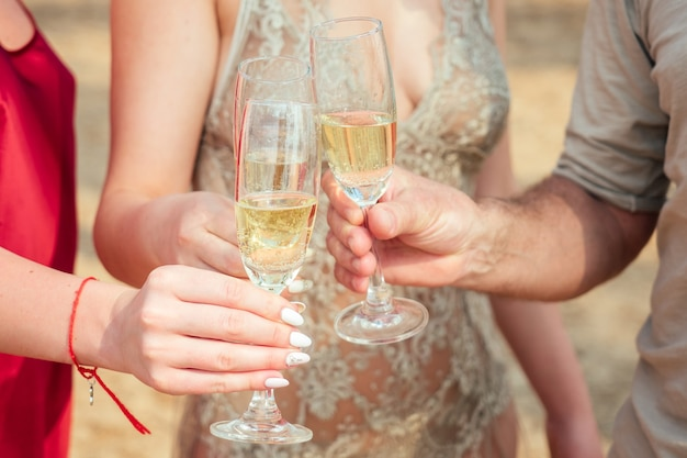 해변에서 샴페인 잔을 들고 축하하는 한 무리의 젊은이들. 휴가 중인 여성과 남성의 손에 스파클링 와인이 든 유리잔.