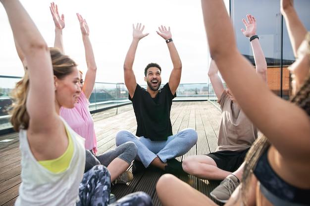 Группа молодых людей, делающих упражнения на открытом воздухе на террасе, концепции спорта и здорового образа жизни.