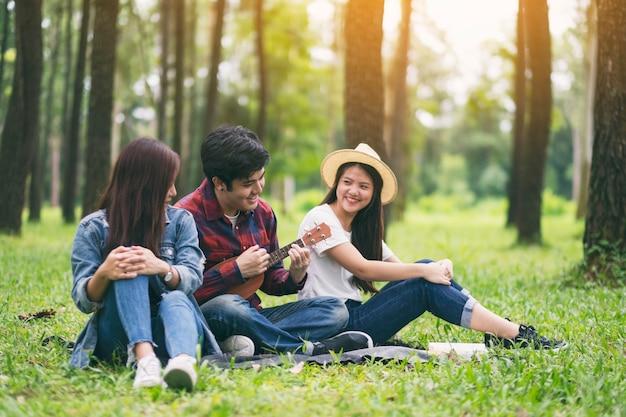 公園で一緒に座ってウクレレを演奏する若者のグループ