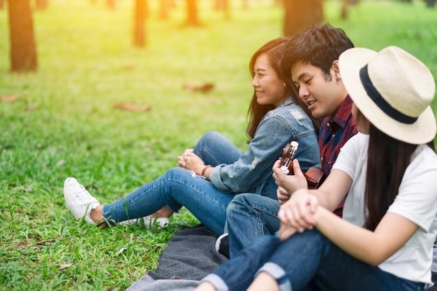 森の中で一緒に座ってウクレレを演奏する若者のグループ