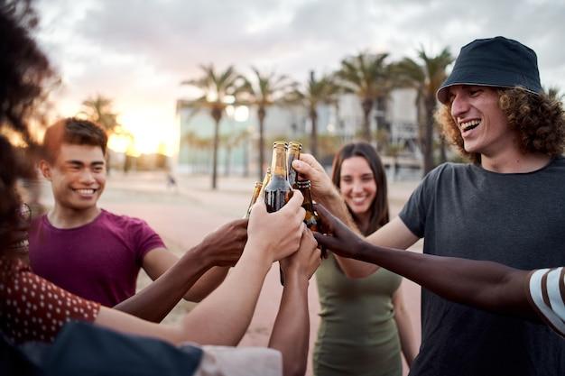 Группа молодых людей с красивыми улыбками поднимает тосты за закат, веселые друзья смешанной расы веселятся