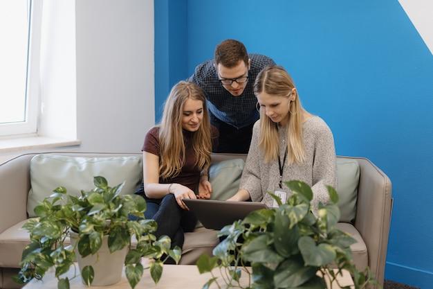 식물 사이의 사무실에서 일하는 젊은 사람들의 그룹