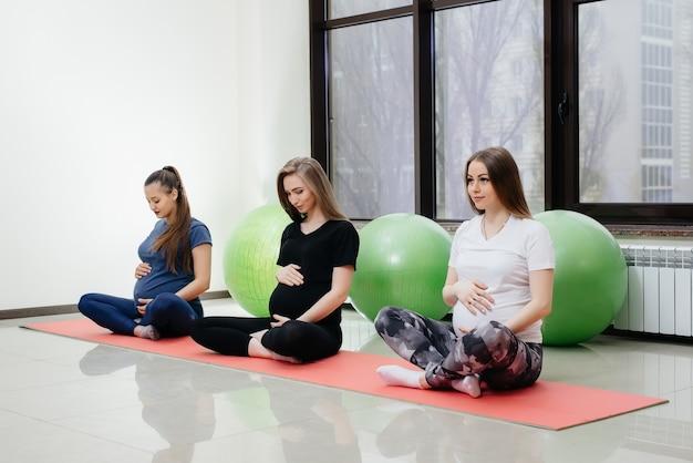 Группа молодых беременных девушек занимается йогой и спортом на крытых ковриках. здоровый образ жизни