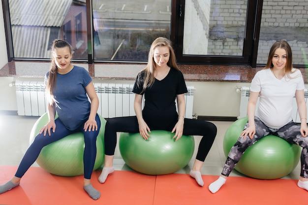 젊은 임신 어머니 그룹은 헬스 클럽에서 필라테스와 공 스포츠에 종사하고 있습니다. 충만한