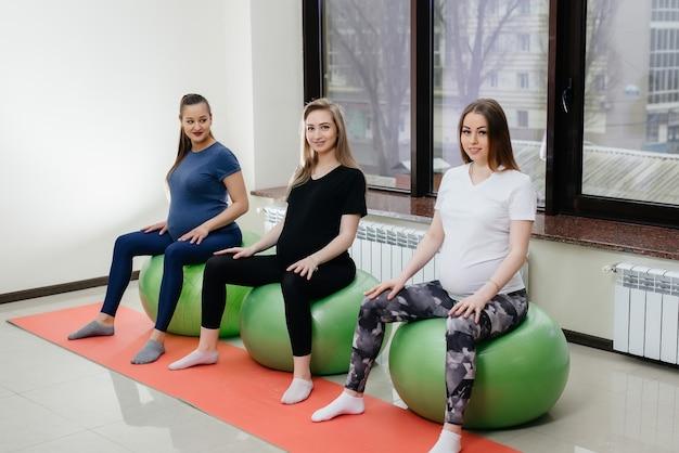 若い妊娠中の母親のグループは、フィットネスクラブでピラティスとボールスポーツに従事しています。妊娠した