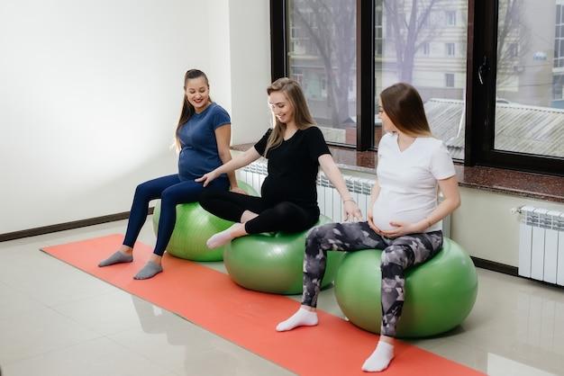 若い妊娠中の母親のグループは、フィットネスクラブでピラティスと球技に従事しています。妊娠中。