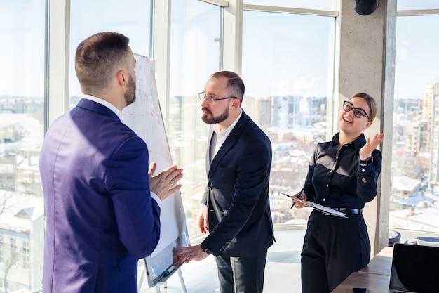 Группа молодых успешных деловых людей анализирует данные с помощью графиков, проводя время в новом современном офисе.