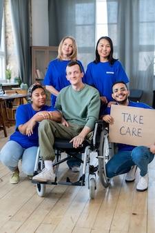 Группа молодых добровольцев и мужчина в инвалидной коляске позируют для фото
