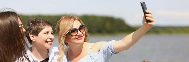 晴れた日を楽しんで、電話で自分撮りをしているボートに乗っている若い女性のグループ