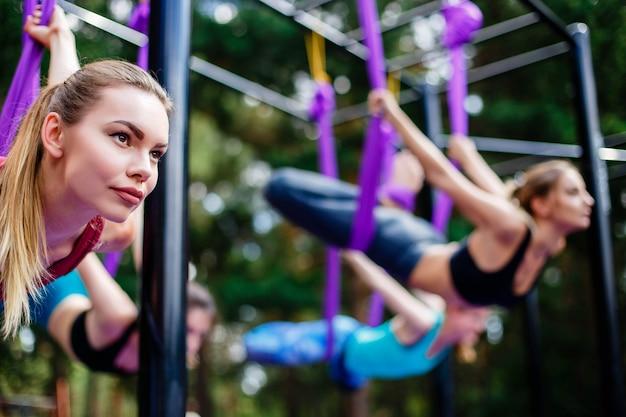Группа молодых женщин выполняет упражнения антигравитационной йоги в парке