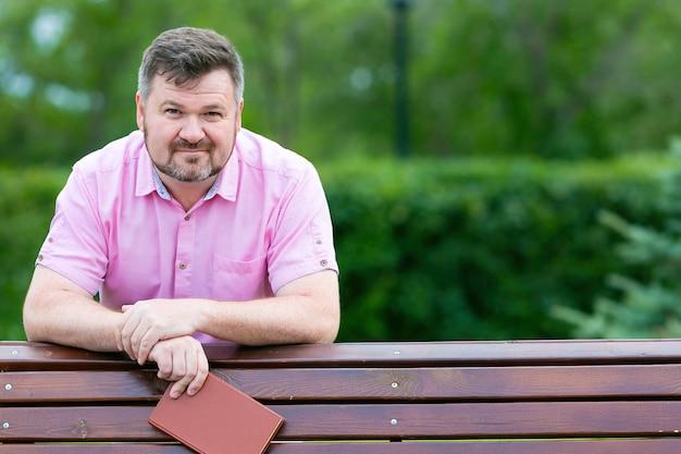 赤いシャツを着たひげを生やした大人の男が公園のベンチにもたれかかっている彼は彼の手で本を持っています