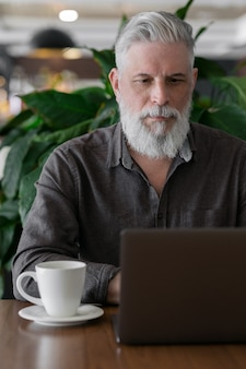 白髪とあごひげを生やした成長した男性は、彼のオフィスや空港の待合室で彼のラップトップで働いています