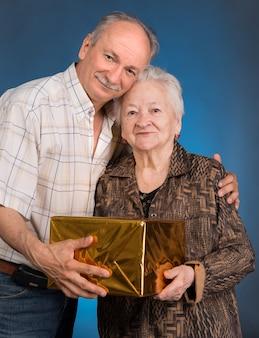 成長した息子とプレゼントボックスを持つ老化したお母さん