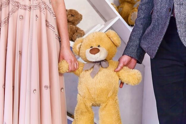 남자와 여자는 봉제 곰의 장난감을 들고 있습니다. 봉제 곰 손을 잡아