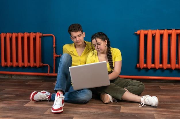 男と女がノートパソコンを手に床に座ってビデオを見ている