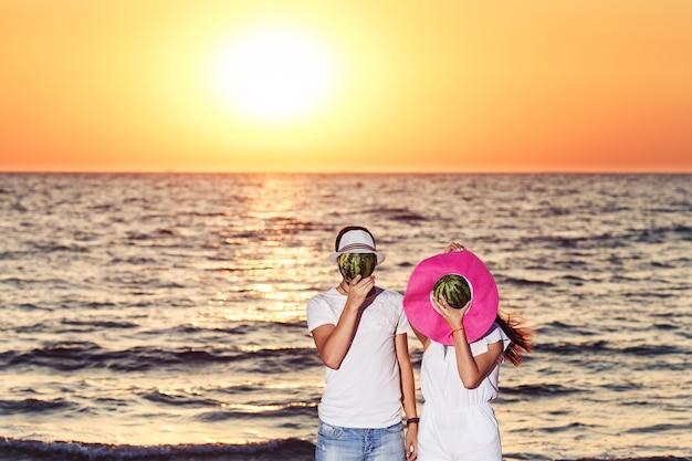 Парень и девушка стоят на пляже и прикрывают головы арбузами в шляпах.