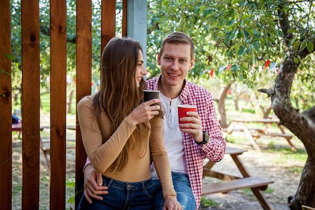 남자와 여자는 카페 테라스에 있는 공원에서 커피를 마신다