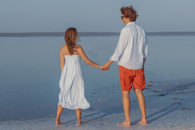 Парень и девушка держатся за руки и смотрят вдаль