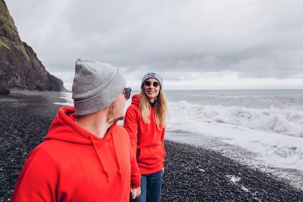 赤いセーターと灰色の帽子をかぶった男と女が黒いビーチで抱いています。アイスランドで幸せなスタイリッシュな笑顔のカップルが歩いてキスします。
