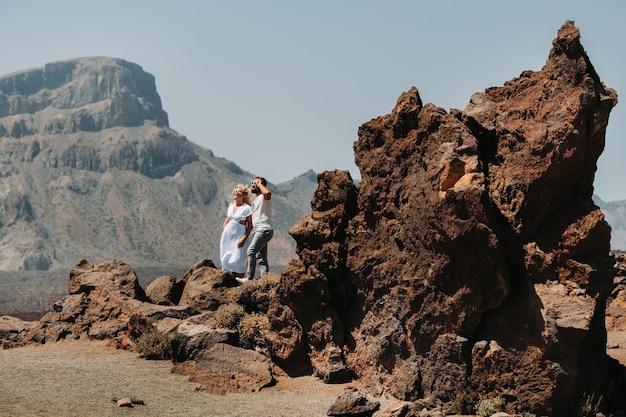 Парень и девушка в белых одеждах и очках стоят в кратере вулкана эль-тейде, пара стоит на горе в кратере вулкана на острове тенерифе, испания.