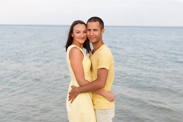 Парень и девушка в желтой одежде стоят в объятиях на пляже